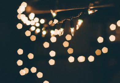 close up string of white Christmas lights on a black background