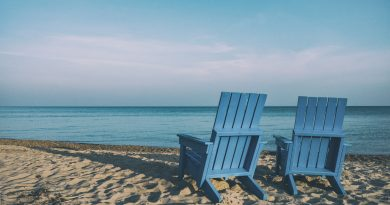 Two blue chairs on the sand before the ocean.